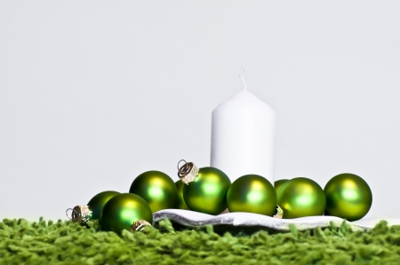 Green christmas balls and white candle