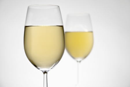 Two glasses of white wine on white background