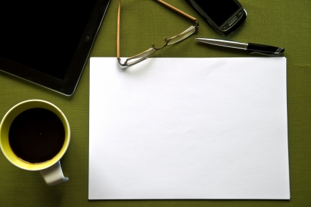 Green desk with coffee, tablet, glasses, phone, pen and a blank paper