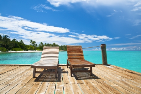 Wooden deck chairs on a tropical beach Stock Photo - 22545054