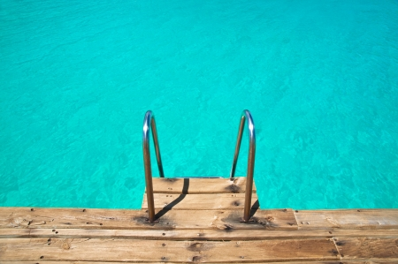 Empty turquoise swimming pool with a ladder Stock Photo