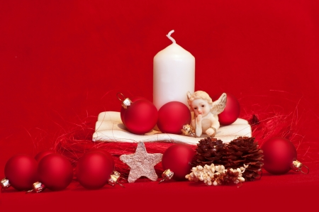 White candle and red christmas balls on red background