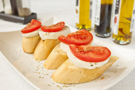 tomatto: A plate with tomato mozzarella italian bruschettas, with olive oil in the background. An Italian breakfast.