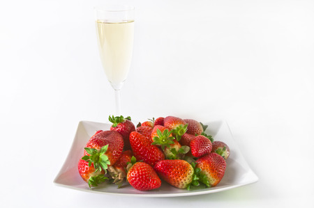 Glass of champagne with plate full of strawberries behind isolated on a white background Stock Photo