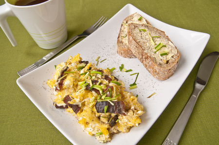 wholesome: Tasty breakfast - scrambled eggs, wholesome bread and tea on green background