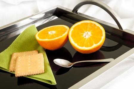 plato del buen comer: postre diet�tico sirve a la cama - dos mitades de naranja y dos galletas Foto de archivo