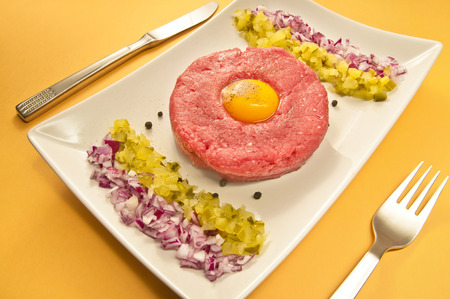european cuisine: Tartar steak - traditional Middle European cuisine.  Raw beef served with egg yolk, pickles and onion.