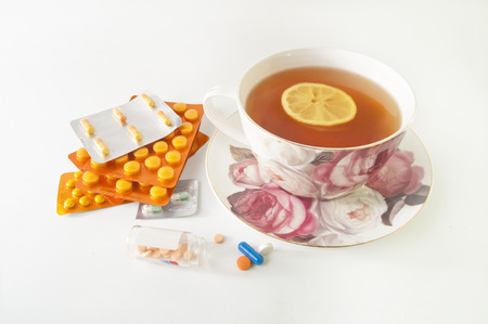 curing: Cup of tea with lemon and a lot of medicines isolated on white - curing cold symptoms