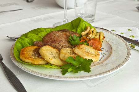 Tasty dinner at a restaurant - roast veal with fried potatoes and assorted vegetables, decorated with lettuce and parsley