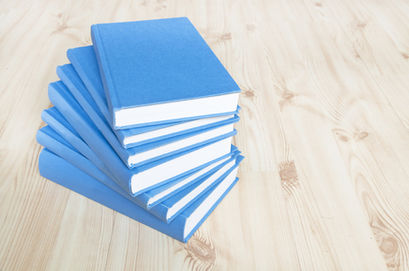 Stack of blue books on wooden floor Stock Photo