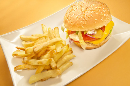 Cheesburger and chips on a plate, yellow background Stock Photo