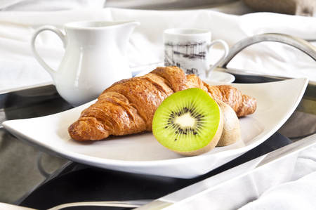 Healthy dessert served directly to bed - kiwi fruits, a croissant and coffee.
