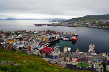 beyond: The northmost city in the world - center of a scandinavian town of Hammerfest visible from a hill, with a seaport in the middle, and industrial district in the background. Beyond the Arctic Circle during the day.