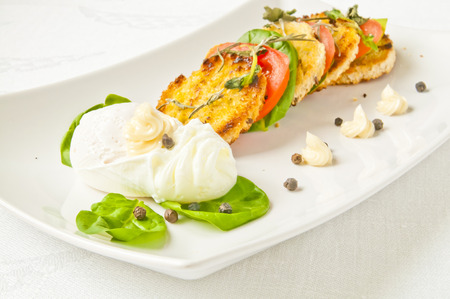 Poached eggs with toasted bread, tomatoes and basilicum leaves. A tasty and stylish breakfast.
