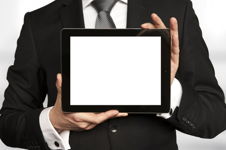computer devices: Man in suit, shirt and tie holding a tablet computer with blank display
