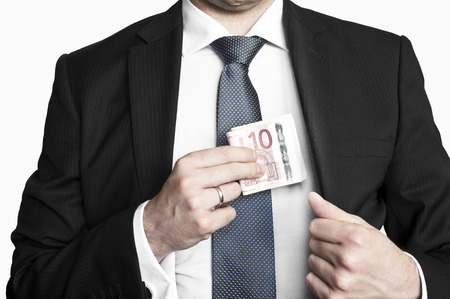 Businessman wearing suit and tie hiding money in his pocket