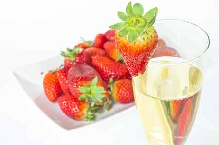 Glass of champagne with plate full of strawberries behind on a white background
