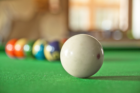 billard: White pool ball with 10 balls in the background on a greeen table