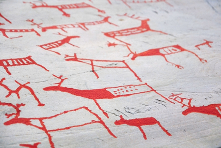 stoneage: Ancient carvings painted in red on gray stone background.