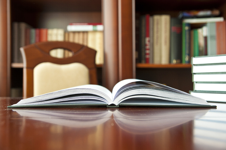 Books on a wooden table - at a library Stock Photo