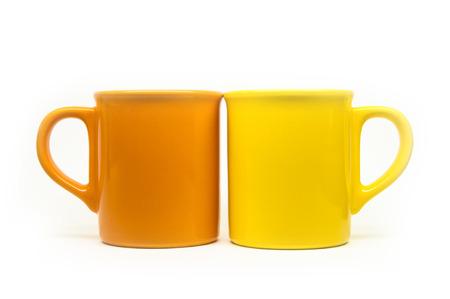 Orange and yellow mugs isolated on white background