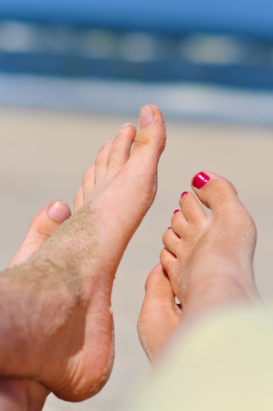 Couple at a beach - womans and mans bare feet
