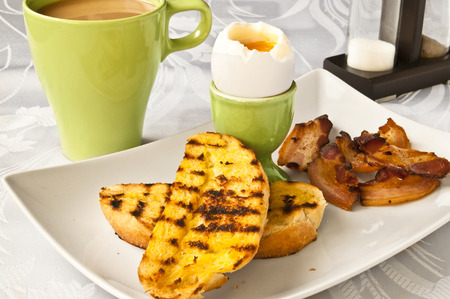 An Enlish breakfast - soft boiled egg, fried bacon, toasts and coffee