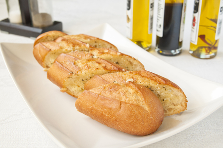 Fresh toasted baguette with garlic butter and olive oil in the background. Stock Photo
