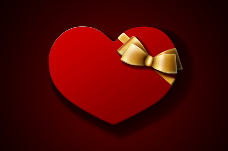 Heart-shaped red gift box with golden bow on dark background. A Valentines Day gift  wedding gift. Stock Photo