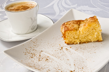 A cup of latte with cinammon and an apple pie.