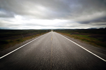 Straight endless road on a cloudy day - chasing the horizon Standard-Bild