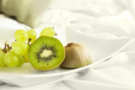 plato del buen comer: Postre sano servido directamente a la cama - frutas verdes sobre fondo blanco. Buena dieta.