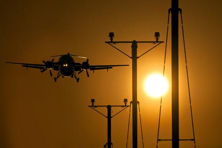 Passenger turbo propeller aircraft approaching the runway at sunset