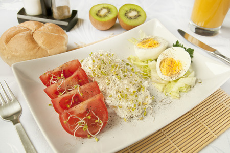 Healthy nutrition - cottage cheese, tomatoes, orange juice, kiwi fruits and hard boiled eggs. Dietary breakfast Stock Photo