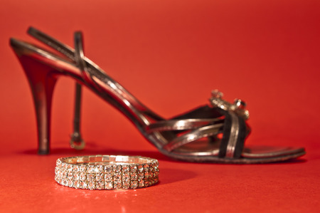 Woman shoe and a bracelet on red background - wealthy Cindirella Stock Photo