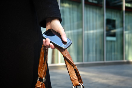 Businesswoman hand holding a phone and a brown bag