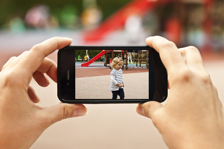 Woman taking a photo of baby girl with smartphone - POV shot Stock Photo