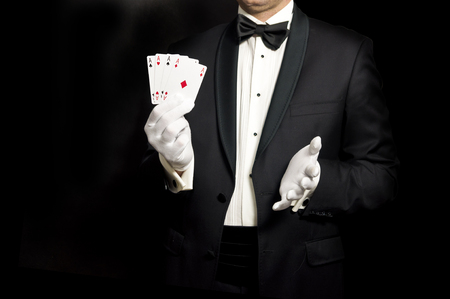 Elegant man in tuxedo holding 4 aces in hand - lucky guy or a magician isolated on black
