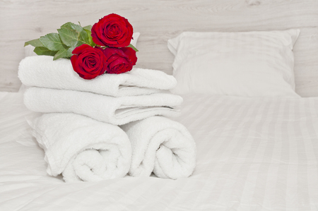 White towels and red roses on a hotel room bed. High quality service. Stock Photo