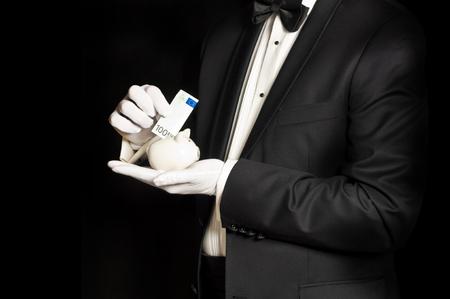 Elegant man in tuxedo holding piggy bank and saving money - isolated on black Stock Photo