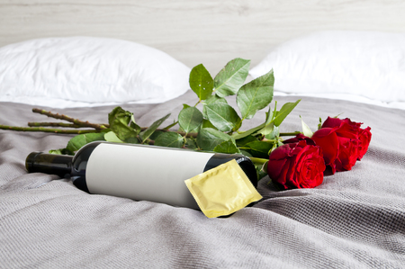 Bottle of wine, red roses and condom on bed - sexy set up