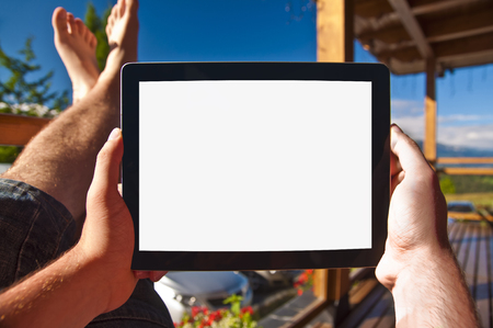 Man on balcony sunbathing, holding a tablet with empty screen - point of view photo