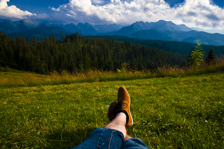 Man relaxing, enjoying mountain landscape on sunny day - point of view shot