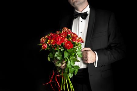 Elegant man in tuxedo holding red roses - isolated on black