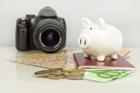 Piggy bank, euro money, passport, camera and map. Saving on travel.