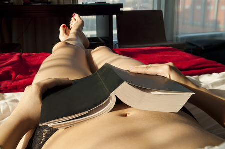 Sexy girl relaxing at home, with a book in her hand, sleeping. Point of view perspective.