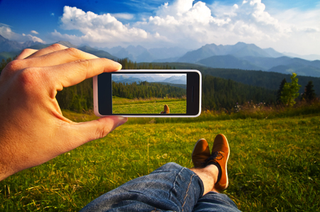 Man taking a photo of a mountain landscape with his phone - point of view shot