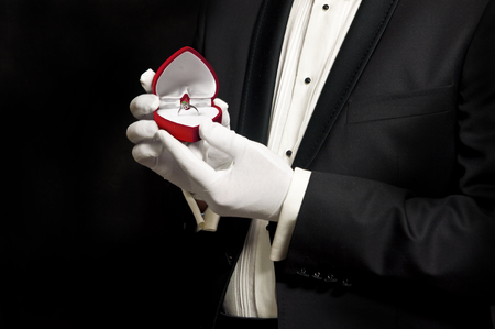 Elegant man in tuxedo holding engagement ring in red heart-shaped box