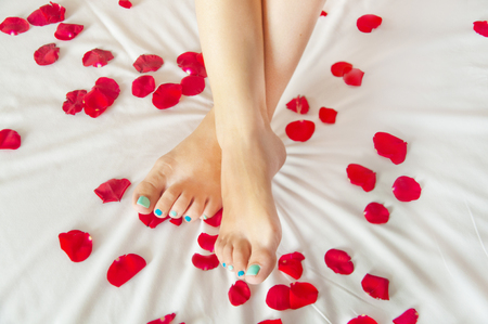 Woman feet on white sheet with rose petals Stock Photo