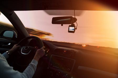 Frau, die ein Auto auf der Autobahn bei Sonnenuntergang fährt, mit Videorecorder neben einem Rückspiegel Standard-Bild